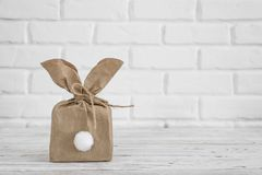 Happy Easter background concept. Flat lay minimalism paper bag same bunny or rabbit for gift or present on white brick wall stock photo