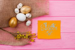 Happy Easter background with decoration. Decorative styrofoam and golden eggs with pussy-willow twig on burlap. Easter greeting card on pink wooden background Stock Image