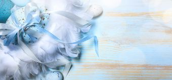 Happy Easter Background; Easter egg and bird feather on table Stock Photo