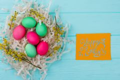 Happy Easter background with eggs in nest. Pussy-willow branches, decorated colorful eggs and paper greeting card. Best wishes for Easter holidays Royalty Free Stock Photography