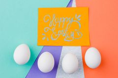 Happy Easter background with eggs. Yellow Easter greeting card and row of white eggs on colorful background. Wishing for happy Easter Royalty Free Stock Photos