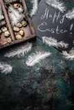 Happy Easter background with feathers , quail eggs and chalkboard , top view stock images