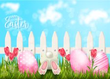Happy Easter background with fence and eggs in grass Royalty Free Stock Photo