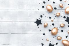 Happy easter background. Flat lay composition with gold eggs. And black stars Stock Photos