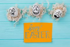 Happy Easter background with funny eggs. White eggs with different drawing face expressions. Wishing for Easter holidays Royalty Free Stock Photo