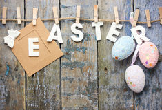 Happy Easter background with hanging Easter eggs. And symbolic text Royalty Free Stock Photos