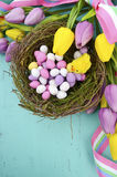 Happy Easter background with painted Easter eggs in birds nest. And yellow and purple silk tulips and ribbon on vintage style rustic distressed aqua blue wood Royalty Free Stock Photo
