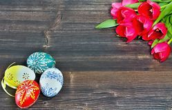 Happy Easter background. A simple background with tulips and Easter eggs for Easter on wooden board Stock Image