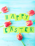 Happy Easter background tulips flowers hand written letters. Green pastel backdrop spring greeting card Stock Photo