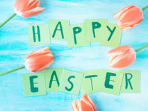 Happy Easter background tulips flowers hand written letters. Green pastel backdrop spring greeting card Royalty Free Stock Images