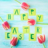 Happy Easter background tulips flowers hand written letters. Green pastel backdrop spring greeting card. Square Royalty Free Stock Photo