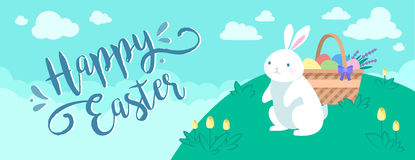 Happy Easter banner. With the white rabbit and the basket of eggs on the lawn on the blue background with clouds Stock Image