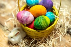 Happy Easter - beautiful, bright, colorful hand-painted Easter eggs in a yellow basket on a natural, wooden background royalty free stock photos