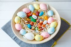 Happy Easter! Bowl with hand painted colorful eggs on white wooden table. Close up. Decoration for Easter stock image