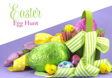 Happy Easter bright color Easter egg hunt theme with yellow, green ribbons and basket of eggs royalty free stock photo