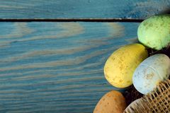 Happy Easter. Bright colored dyed eggs on the bottom on a blue wooden surface. stock images