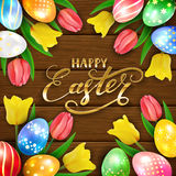 Happy Easter on brown wooden background with eggs and tulips Royalty Free Stock Images