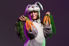 Happy Easter bunny girl a bunch of carrots. Thoughtful girl in a full body bunny suit with big ears. Holding carrots. Dark colored background Stock Photo