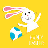 Happy Easter. Bunny rabbit hareand blue painted egg in the paper pocket. Baby greeting card. Yellow background. Flat design. Stock Photo