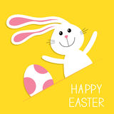Happy Easter. Bunny rabbit hareand pink painted egg in the paper pocket. Baby greeting card. Yellow background. Flat design. Stock Photo