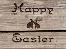 Happy Easter - burned an inscription on a wood. Royalty Free Stock Photo