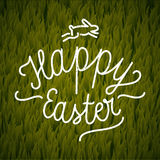 Happy Easter calligraphy. vintage label on grass background. Stock Photography