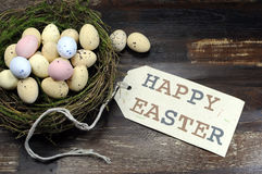 Happy Easter candy easter eggs in birds nest on dark vintage recycled wood with tag