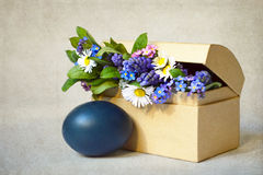 Happy Easter card: Blue Easter egg and spring flowers on grunge background  Stock Images