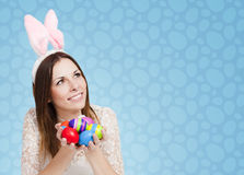 Happy Easter card blue. Excited girl holding bunch of painted eggs on blue background Stock Photography