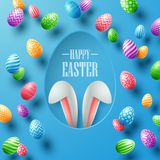 Happy Easter card with bunny ears hiding in egg hole and colorful eggs on blue background Stock Image