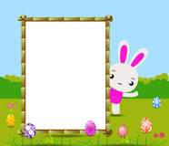 Happy Easter card with eggs and rabbits nearby wood board Royalty Free Stock Photo