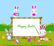 Happy Easter card with eggs and rabbits nearby wood board Stock Photo