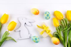 Happy Easter card. Frame with yellow tulips and easter eggs and bunny with copy space for text on white background. royalty free stock photos