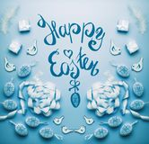 Happy Easter card with handwritten text lettering eggs and decoration on blue background, top view, flat lay royalty free stock images