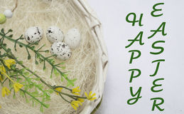 Happy easter card,. Wicker basket with quail eggs,shavings, chicken,willow twig and bird on the white background. happy easter card Stock Photo
