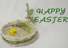 Happy easter card,. Wicker basket with quail eggs,shavings, chicken,willow twig and bird on the white background. happy easter card Royalty Free Stock Photography