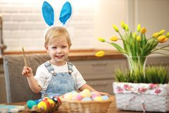 Happy easter! child paints eggs Royalty Free Stock Images