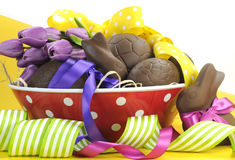 Happy Easter chocolate Easter eggs and bunny rabbit hamper with colorful polka dot and stripe ribbon in red polka dot bowl. With sample text greeting or copy Stock Photo