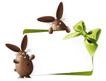 Happy easter, chocolate funny bunnies showing the gift card with Royalty Free Stock Image