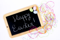 Happy Easter. Colored eggs and blackboard with wooden edge for a happy Easter Stock Photography