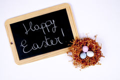 Happy Easter. Colored eggs and blackboard with wooden edge for a happy Easter Stock Photo