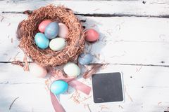 Happy Easter. Colorful Easters eggs in a nest with feathers and a chalk board on the wooden backgound. Happy Easter. Colorful Easters eggs in a nest with royalty free stock photo