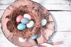 Happy Easter. Colorful Easters eggs in a nest with feathers and a chalk board on a wooden stump. Happy Easter. Colorful Easters eggs in a nest with feathers and royalty free stock images
