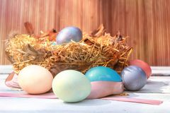 Happy Easter. Colorful Easters eggs in a nest with feathers on the wooden backgound. Happy Easter. Colorful Easters eggs in a nest with feathers on the wooden stock photo