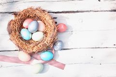 Happy Easter. Colorful Easters eggs in a nest with feathers on the wooden backgound. Happy Easter. Colorful Easters eggs in a nest with feathers on the wooden stock photography
