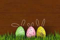 Happy Easter. Colorful, funny, cute bunny decorated quail Easter eggs, grass on wooden background. Design template for. Banner, flyer, invitation Stock Photos