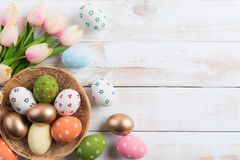 Happy easter! Colourful of Easter eggs in nest with pink tulip flower and Feather on wooden background royalty free stock photo