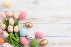 Happy easter! Colourful of Easter eggs in nest with pink tulip flower and Feather on wooden background royalty free stock images