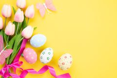 Happy easter! Colourful of Easter eggs in nest with pink tulip flower and Feather on yellow paper background.  royalty free stock image