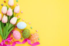 Happy easter! Colourful of Easter eggs in nest with pink tulip flower and Feather on yellow paper background.  royalty free stock photography